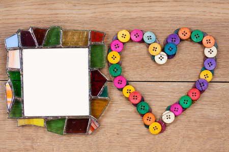 Glass frame and heart shape of color buttons on wooden background photo