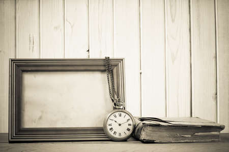Vintage pocket watch, photo frame, book on a table in front of wooden background photo