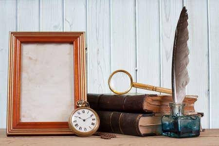 Antico orologio da tasca, penna e calamaio, libri, cornice per foto, lente di ingrandimento su un tavolo di fronte a sfondo in legno