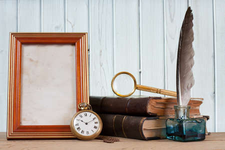 Antique pocket watch, quill and inkwell, books, photo frame, magnifying glass on a table in front of wooden background