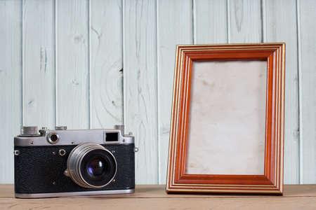 photo camera: Macchina fotografica d'epoca e cornice di fronte a sfondo in legno