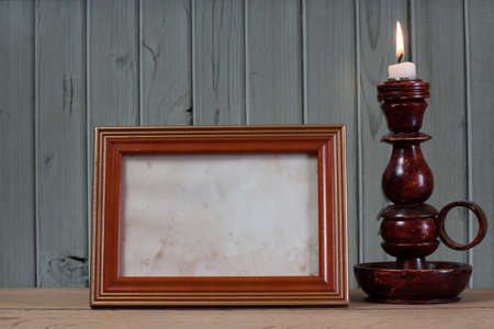 burning time: Photo frame and candlestick with burning candle in front of wooden background Stock Photo