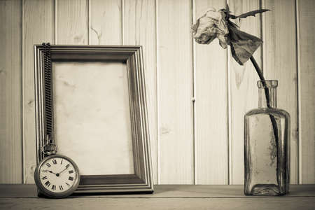 vintage bottle: Dried flower in vintage bottle, pocket watch and photo frame in front of wooden background Stock Photo