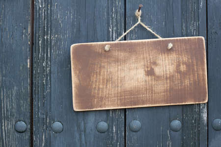 welcome door: Grunge wood frame blank with rope hanging on nail on dirty planks background Stock Photo