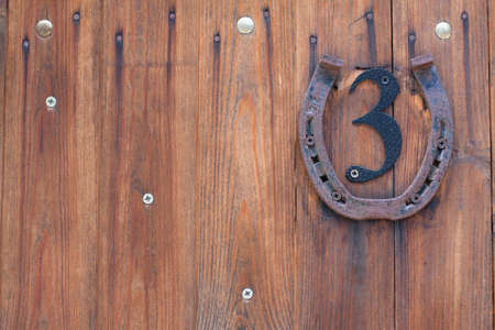 Wooden planks background with metal number three and rusty horseshoe photo