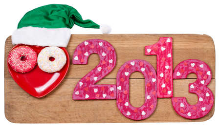 New Year 2013 snake date with green hat on wooden board isolated on white background Stock Photo - 16997746