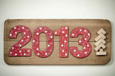 Retro New Year 2013 date and tree handmade on wooden board background photo