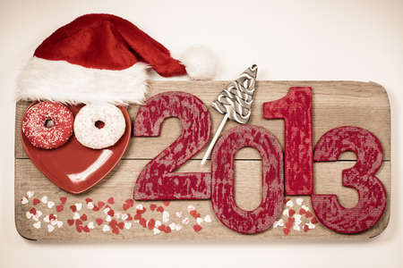 Vintage New Year 2013 handmade snake date with Santa hat on wooden board photo