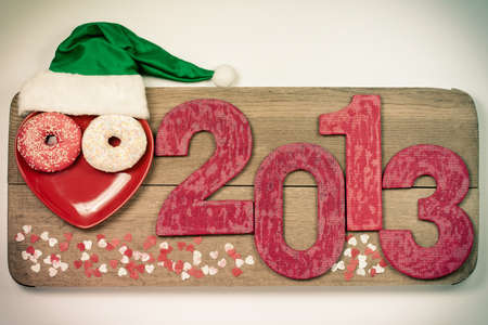 Vintage New Year 2013 snake date with green hat on wooden board Stock Photo - 16997755