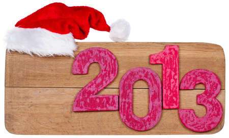 Retro New Year 2013 date and santa hat on wooden texture board background photo