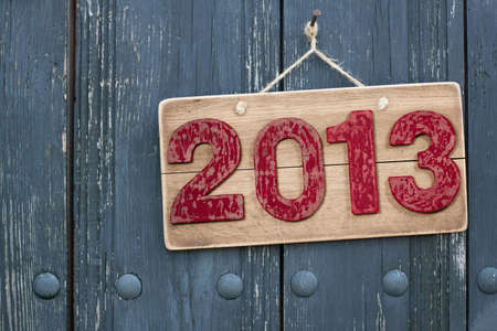 Vintage New Year 2013 date on wooden board background with rope hanging on nail photo