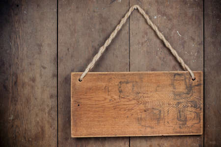Wooden signboard with rope hanging on grunge planks background Stockfoto