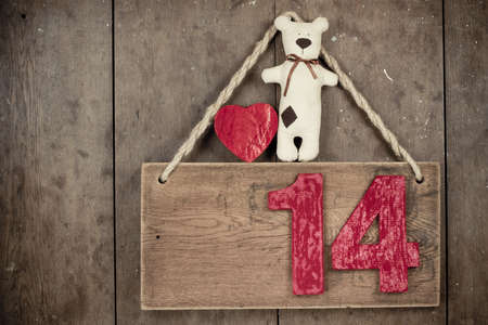 Valentine heart, handmade bear,  fourteen on wooden signboard with rope hanging on planks background