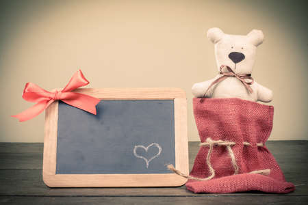 Toy bear, chalk heart on wooden black board with bow in vintage style Stock Photo - 17627753