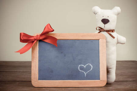 Valentine card with toy bear, heart on wooden black board with bow in vintage style photo
