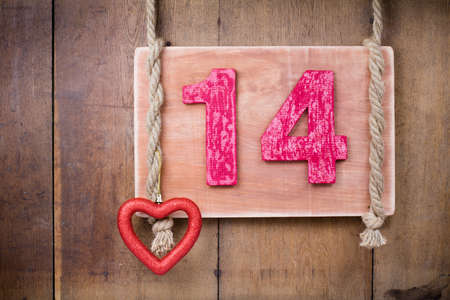 Valentine heart, wood signboard and number fourteen with rope hanging on planks background photo