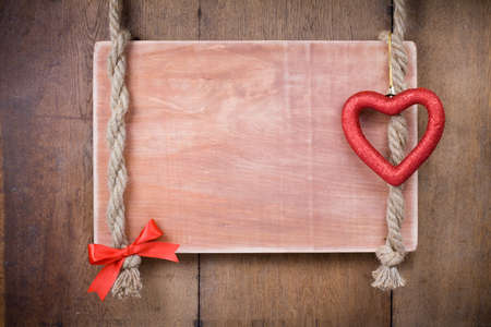 Valentine heart, bow, wooden signboard with rope hanging on planks background photo