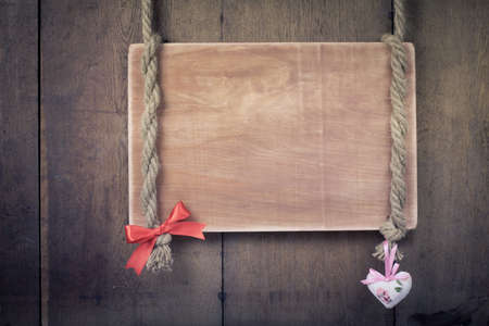 Wooden signboard frame on rope with heart and bow valentine background photo