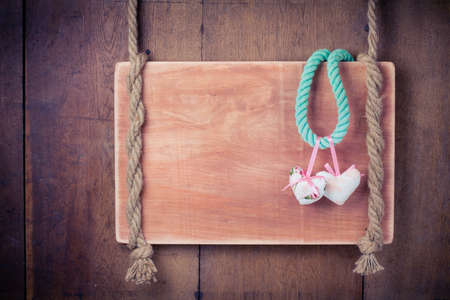 Valentine hearts with bows, wooden signboard hanging on rope on old wooden wall background photo
