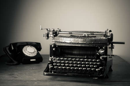 Vintage old typewriter, phone on table desaturated photo Imagens