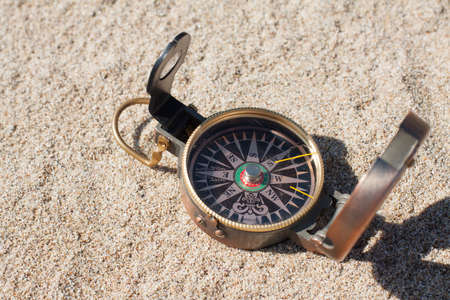 Vintage compass on sand background photo