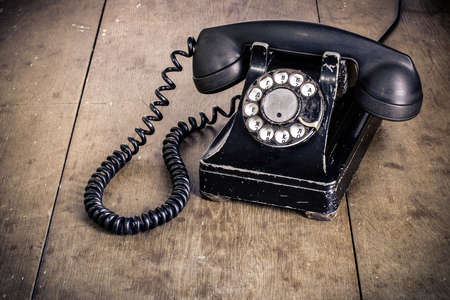 Vintage black phone on old wooden table background photo