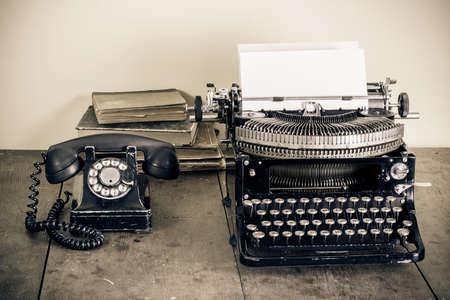 Vintage phone, alte Schreibmaschine, Bücher auf dem Tisch desaturated photo Standard-Bild