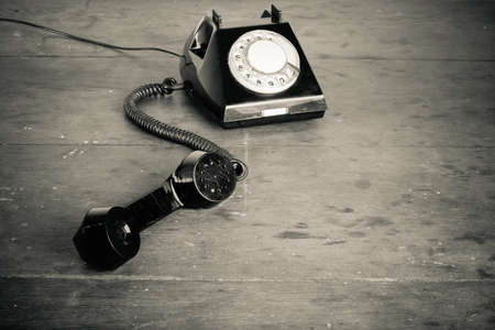 Old retro phone with rotary disc on wooden table grunge background photo