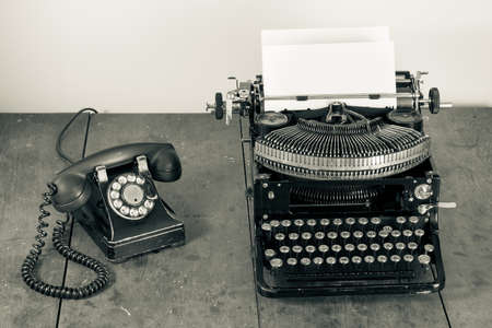 type writer: Vintage phone, old typewriter on table desaturated photo