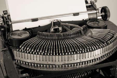 secretarial: Vintage old typewriter and paper blank closeup desaturated photo