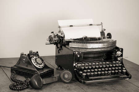Vintage phone, old typewriter on table desaturated photo Stock Photo - 17627798