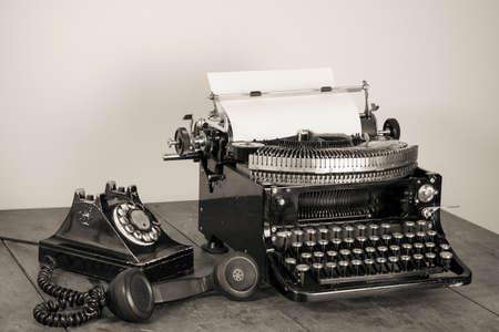key words art: Vintage phone, old typewriter on table desaturated photo
