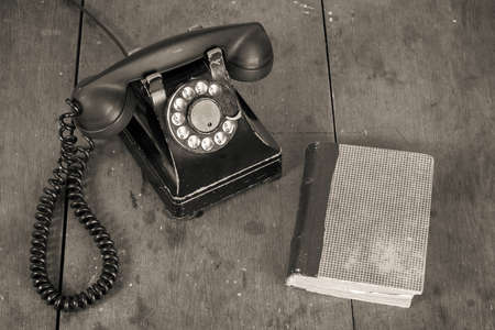 Old vintage phone, book on wooden table grunge background Banco de Imagens