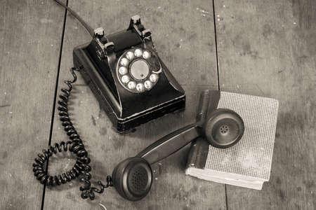 Vintage telefoon, boek over oude tafel grunge achtergrond Stockfoto