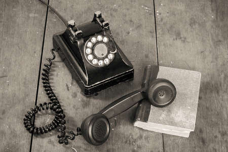 Vintage telephone, book on old table grunge background