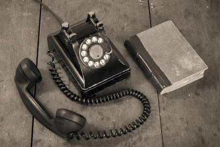 telephone cable: Old vintage phone, book on wooden table grunge background Stock Photo