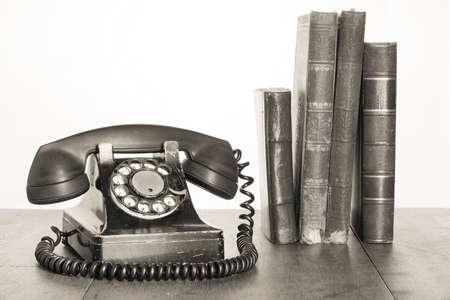 PHONE LINE: Vintage phone, old books on table sepia photo