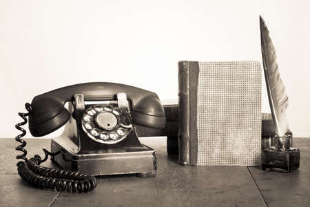 retro phone: Vintage phone, old book, quill and inkwell on wooden table sepia photo Stock Photo