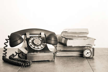 old time: Vintage phone, old clock, books on table sepia photo Stock Photo