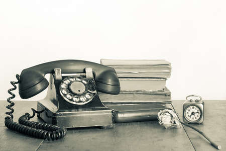 Retro phone, books, clock, dry flower on wooden table sepia photo photo