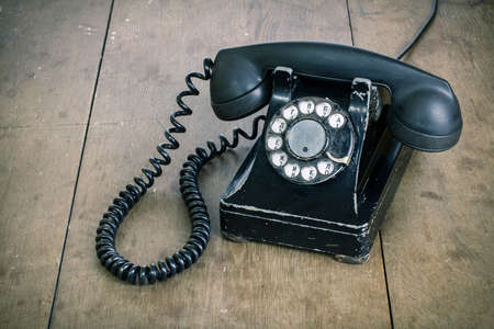 Black vintage phone on old wooden table background
