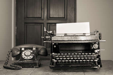 Vintage phone, old typewriter on table desaturated photo