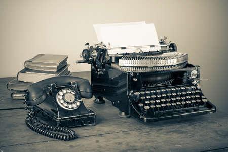 Telefono d'epoca, vecchia macchina da scrivere, i libri sul tavolo foto desaturata Archivio Fotografico