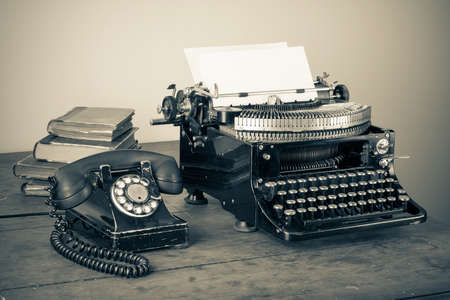 key words  art: Vintage phone, old typewriter, books on table desaturated photo