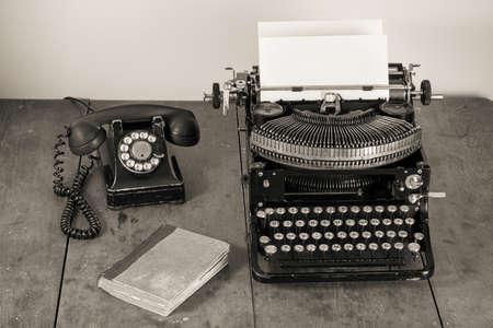 Vintage (1940.) Alte Schreibmaschine, Telefon, Buch auf dem Tisch desaturated photo Standard-Bild