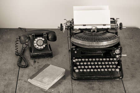 Vintage (1940th) old typewriter, phone, book on table desaturated photo Banco de Imagens