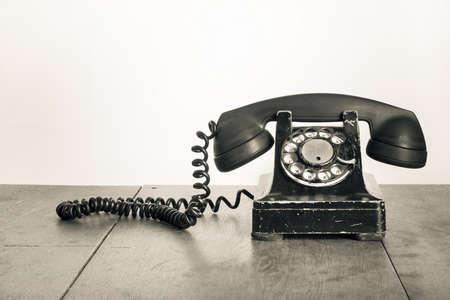 Vintage telefoon op oude tafel sepia foto
