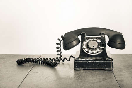 rotary dial telephone: Vintage telephone on old table sepia photo Stock Photo