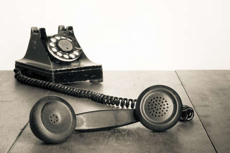 Vintage telephone handset on old table sepia photo Imagens