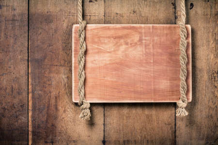 Wooden signboard with rope hanging on grunge planks background photo